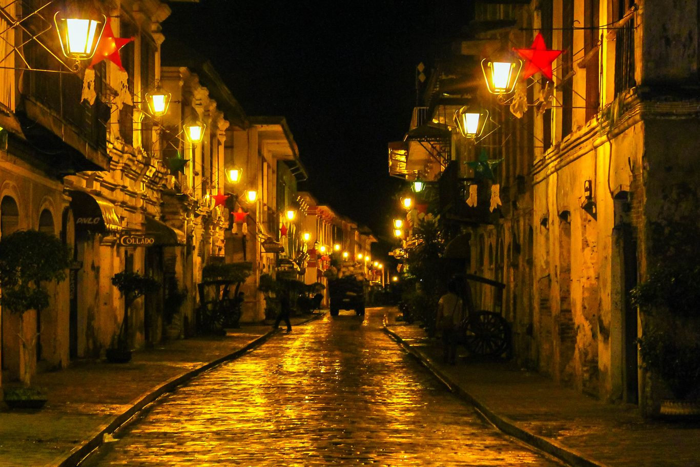 At night, a horse-drawn carriage moves along a cobblestone street lined on either side by old stone houses, upon which are hung lit lampposts
