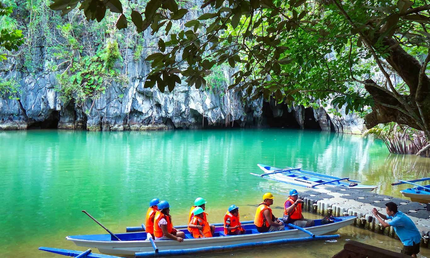 A tourist boat full of people sails along turquoise waters and into a cave on limestone cliffs overhung with dense vegetation