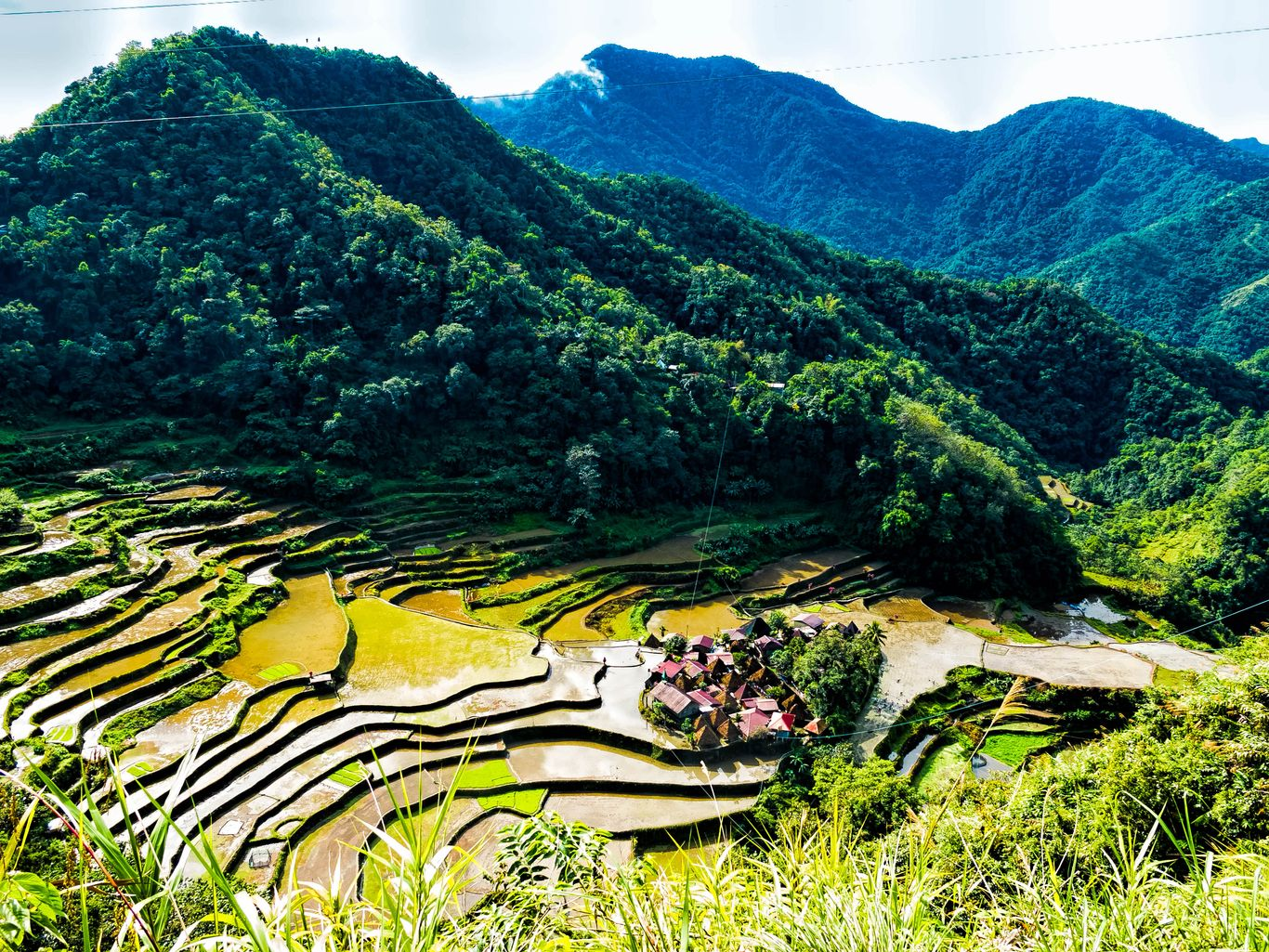 A small traditional village lies nestled at the foot of rice terraces carved on the slope of a mountain, surrounded by forested hills and mountains