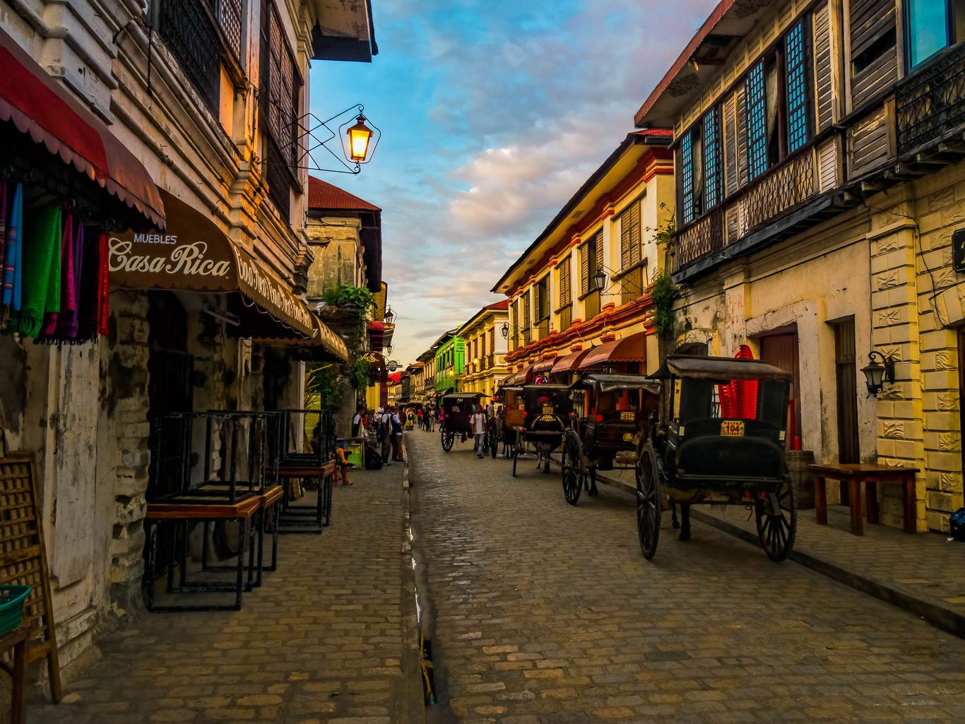 Horse-drawn carriages lined up on a cobblestone street bounded on either hand by old brick and wood houses at the Historic City of Vigan, one of the UNESCO World Heritage Sites in the Philippines