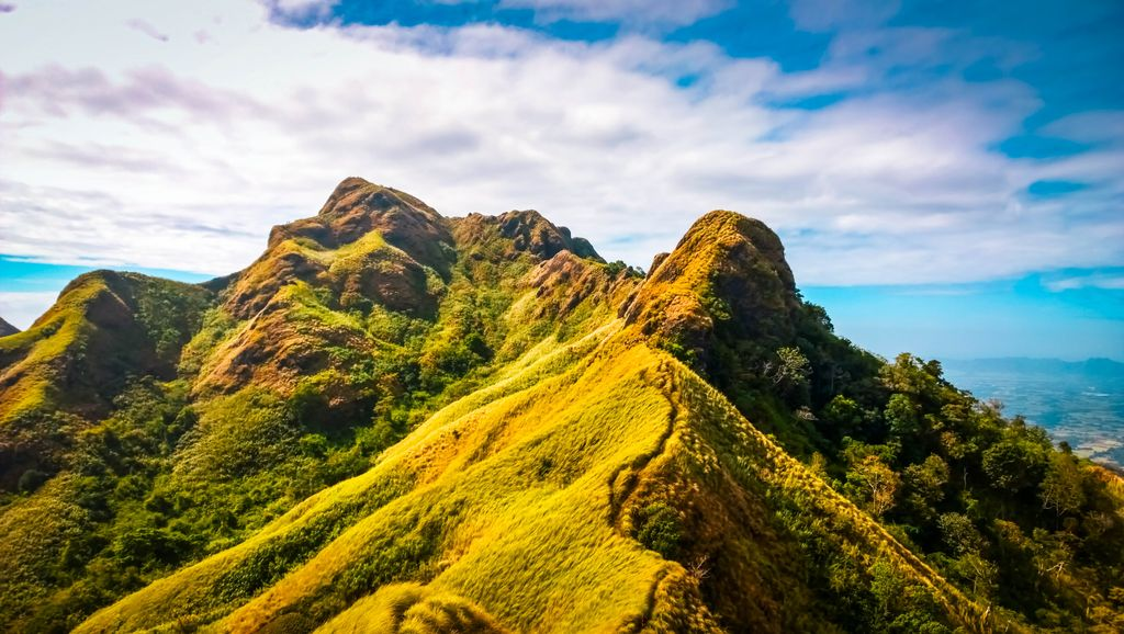 A winding trail leads through the top of a rugged, craggy, and grass-clad ridge of Mount Batulao, the southwestern terminus of the Tagaytay Ridge, one of the mountain ranges of the Philippines