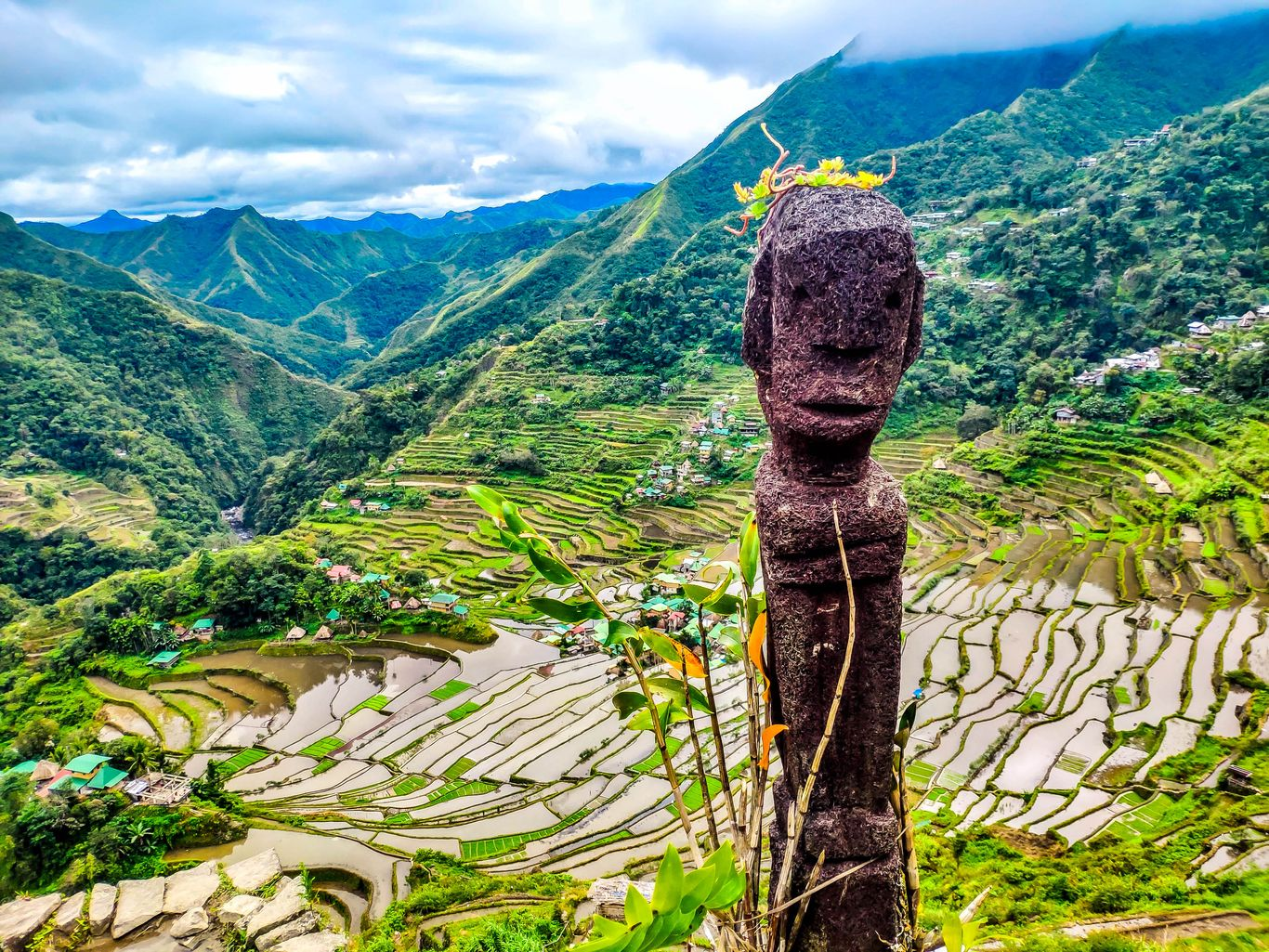 A carved wooden idol backdropped by a cluster of rice terraces carved on a semicircular fashion along the slopes of a mountain fronting a forested ranges