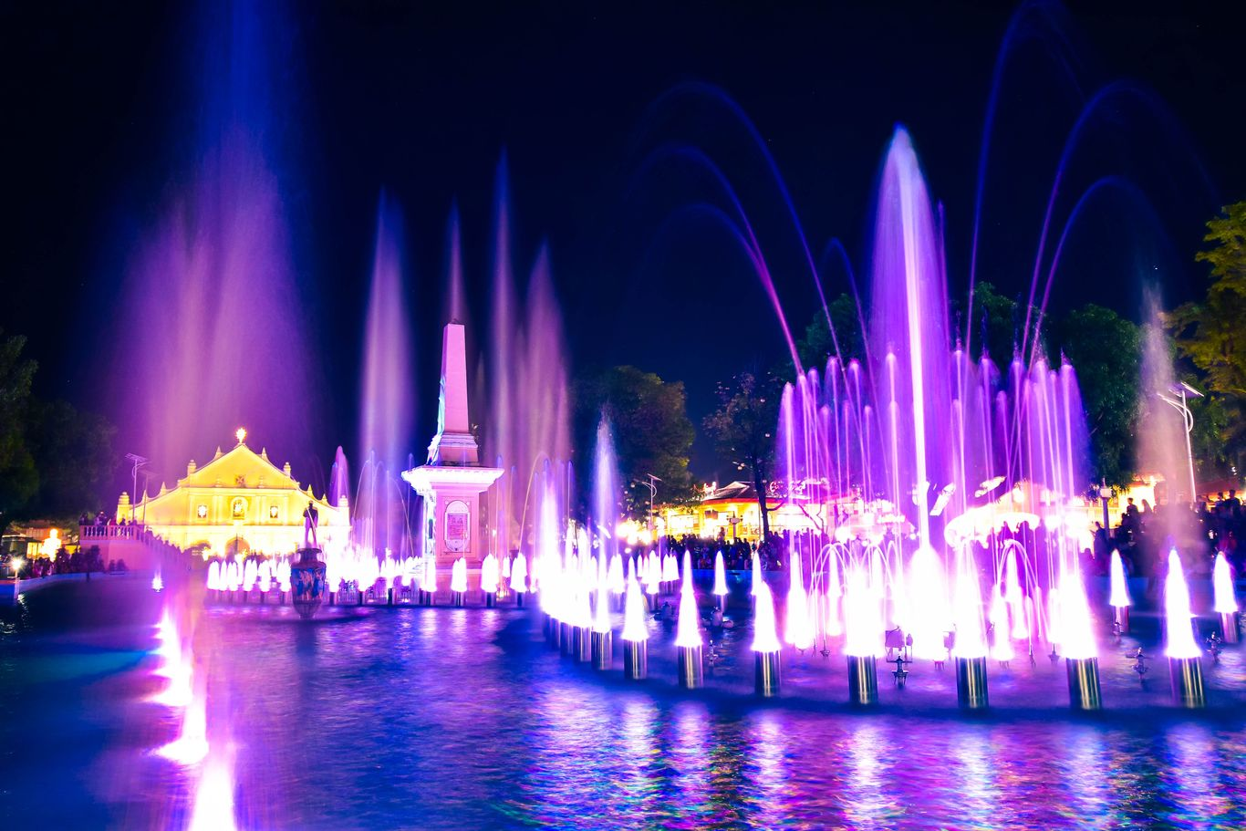 Spurting fountains illuminated by lights at night