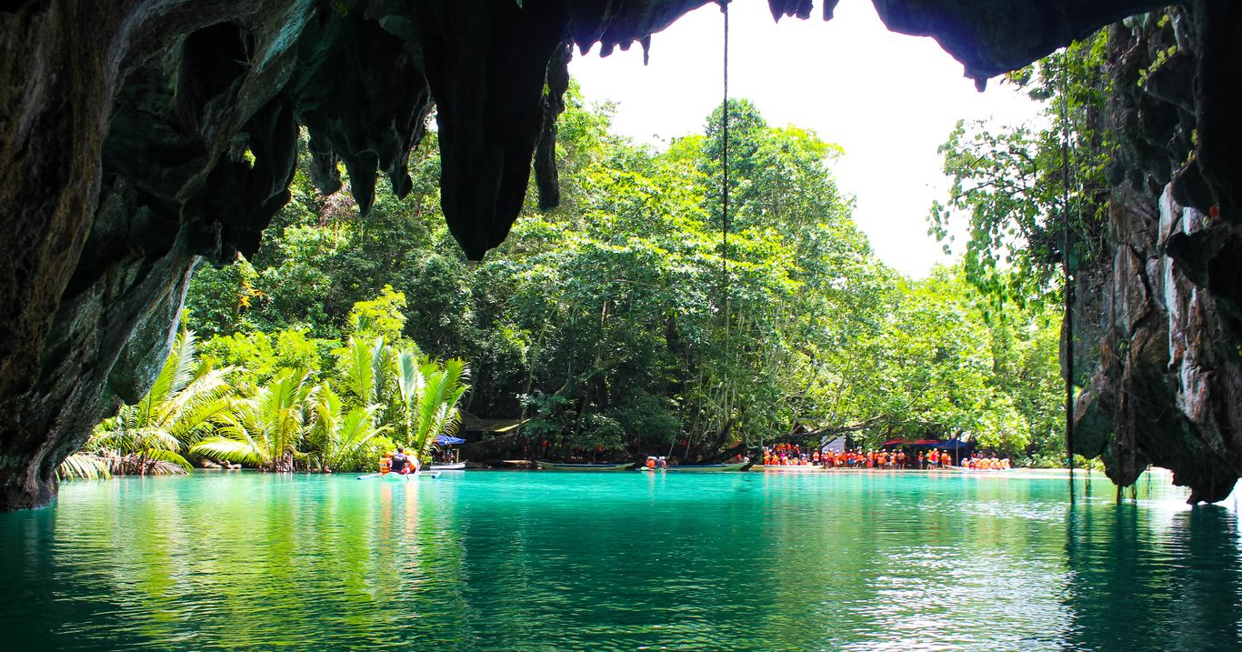 Turquoise body of water emerges out of a cave and into open daylight at the Puerto Princesa Subterranean River National Park, one of the UNESCO World Heritage Sites in the Philippines