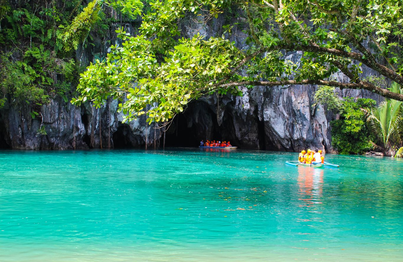 Tourist boats full of people sail along turquoise waters and into a cave on limestone cliffs overhung with dense vegetation