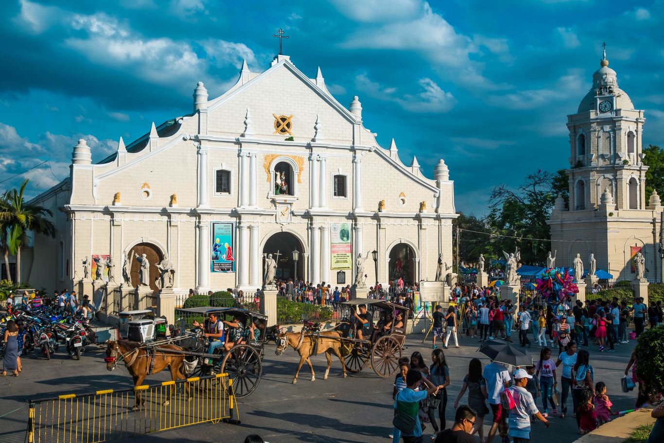 A couple of horse-drawn carriages and a crowd of people pass by a stone church with a white facade and a white bell tower in the Historic City of Vigan, one of the UNESCO World Heritage Sites in the Philippines