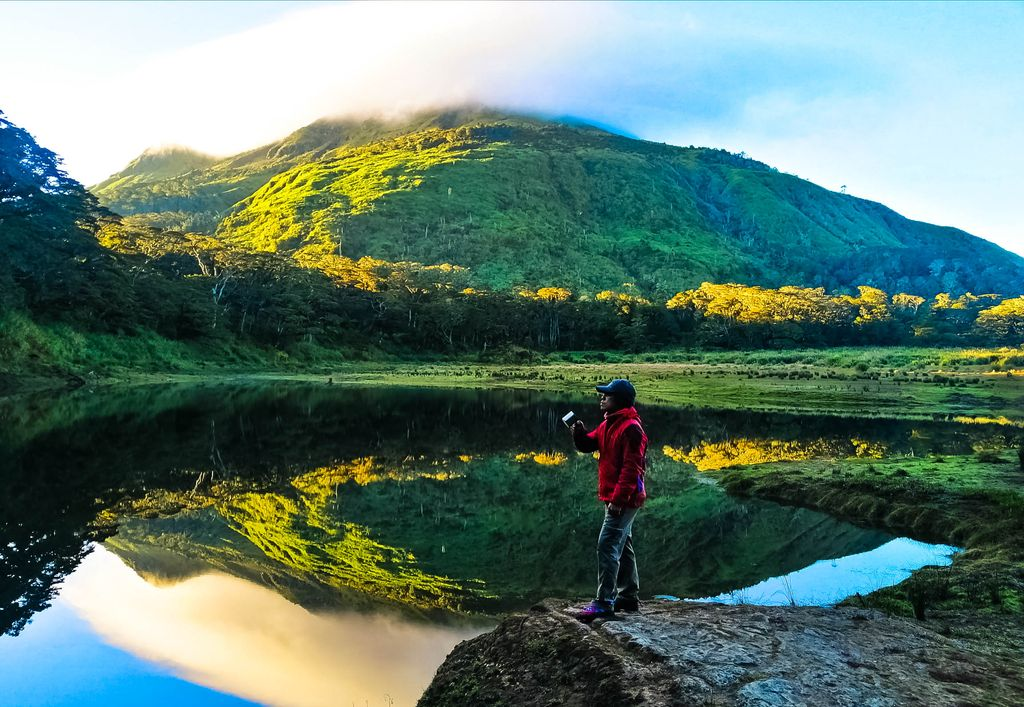 A man drinks his coffee while standing on the shores of a lake, upon whose utterly crystalline surface is reflected the forested mountain Apo of the Pantaron Mountain Range, one of the mountain ranges of the Philippines