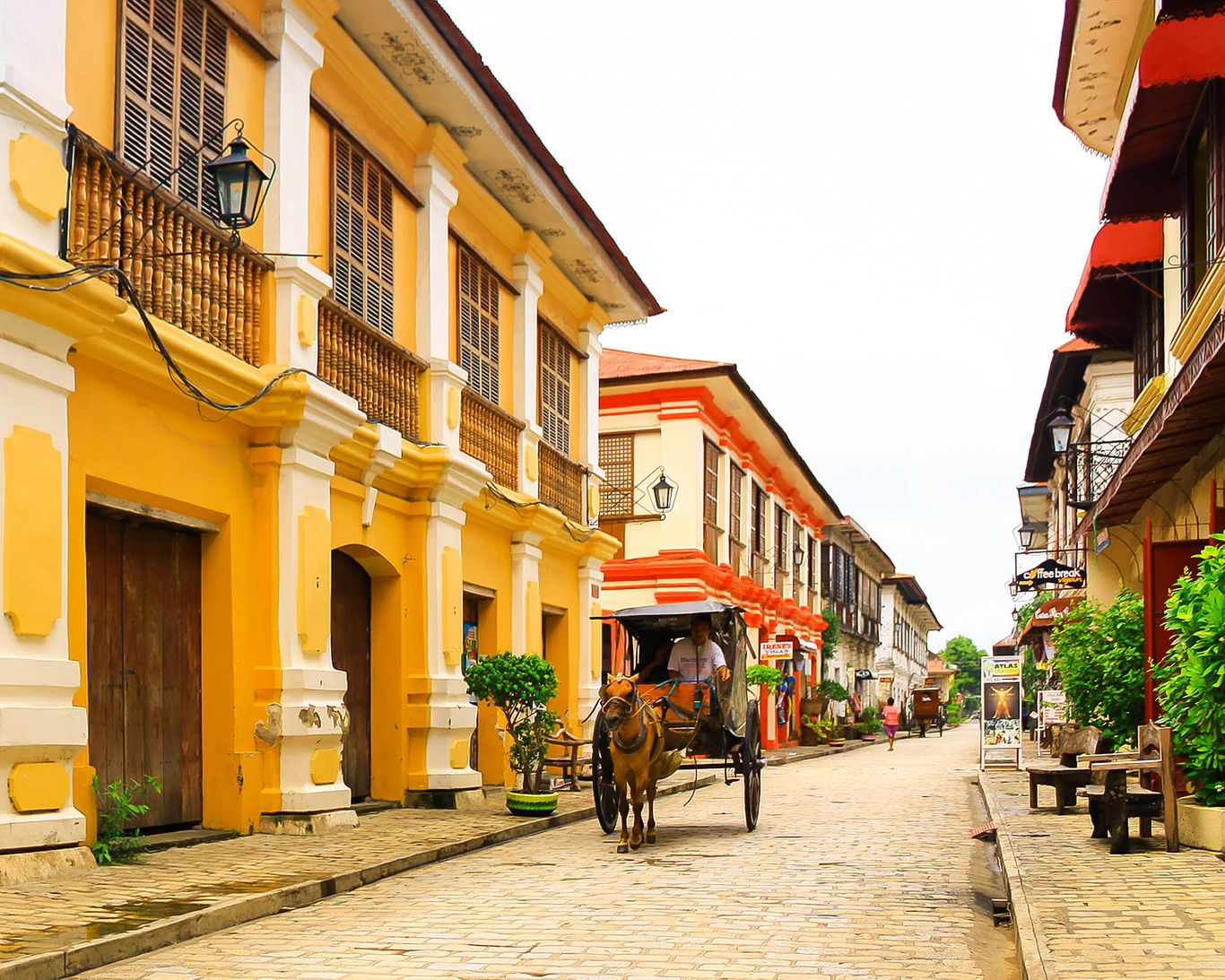A horse-drawn carriage moves along a cobblestone street, past old two-story houses wrought of stone, brick, and wood at the Historic City of Vigan, one of the UNESCO World Heritage Sites in the Philippines