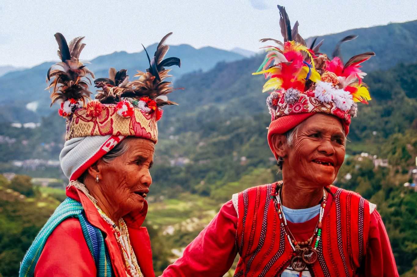 A couple attired in their colorful tribal gear and clothing, backdropped rice terraces carved on a mountainous valley