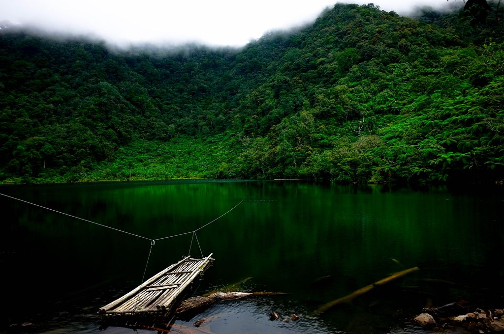 A deep and dark lake with emerald waters, ringed round by the forested and mist-clad mountains