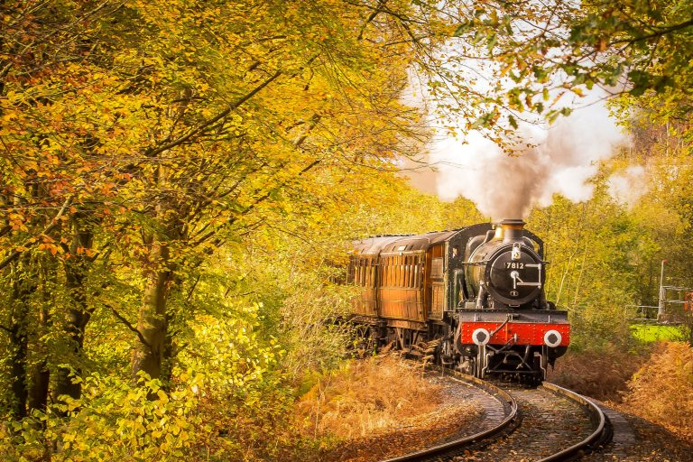 """A steam train moves along an old railway surrounded by trees in autumn season, used as a Featured Image for the article entitled """"Fernweh: When You Feel Homesick for Places You Have Never Been to"""" by phmillennia"""