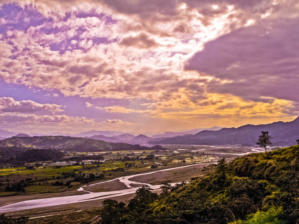 A river winding through fields backdropped by hills and mountains beneath a cloudy, dusky sky