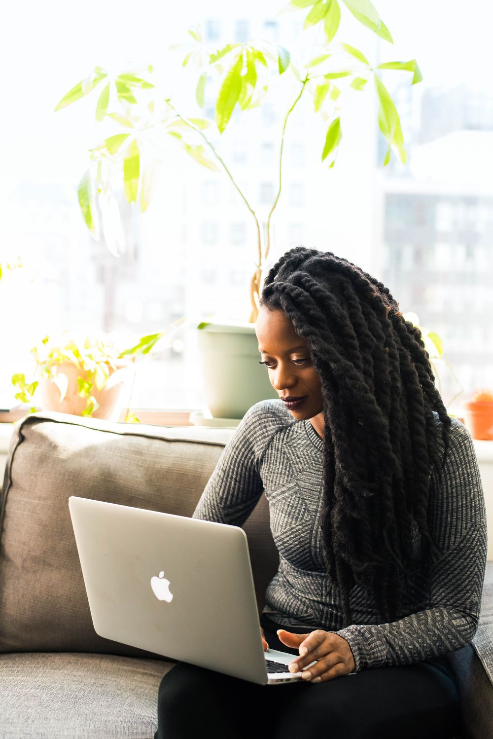 A woman with long, braided hair uses a laptop while sitting on a couch; she is perhaps a social media manager, one of the best jobs that allow you to work from home