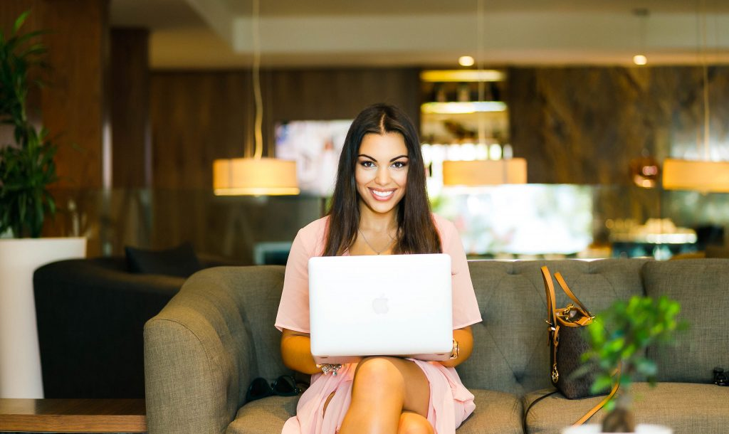 A woman in a pink dress smiles at the camera while she sits on a leather couch with a laptop on her lap, perhaps happy that she has found one of the best jobs that allow you to work from home