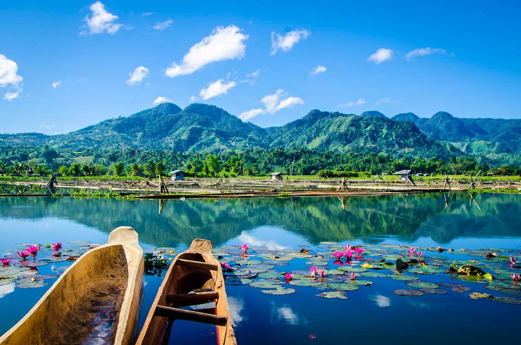 Wooden boats on the surface of a crystal clear lake, backdropped by a green mountain range