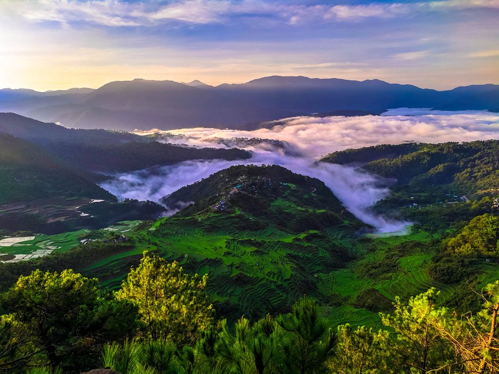 The sun rises over a mountain village with verdant rice terraces, surrounded by lofty ranges, and covered with rolling mantles of cloud and fog