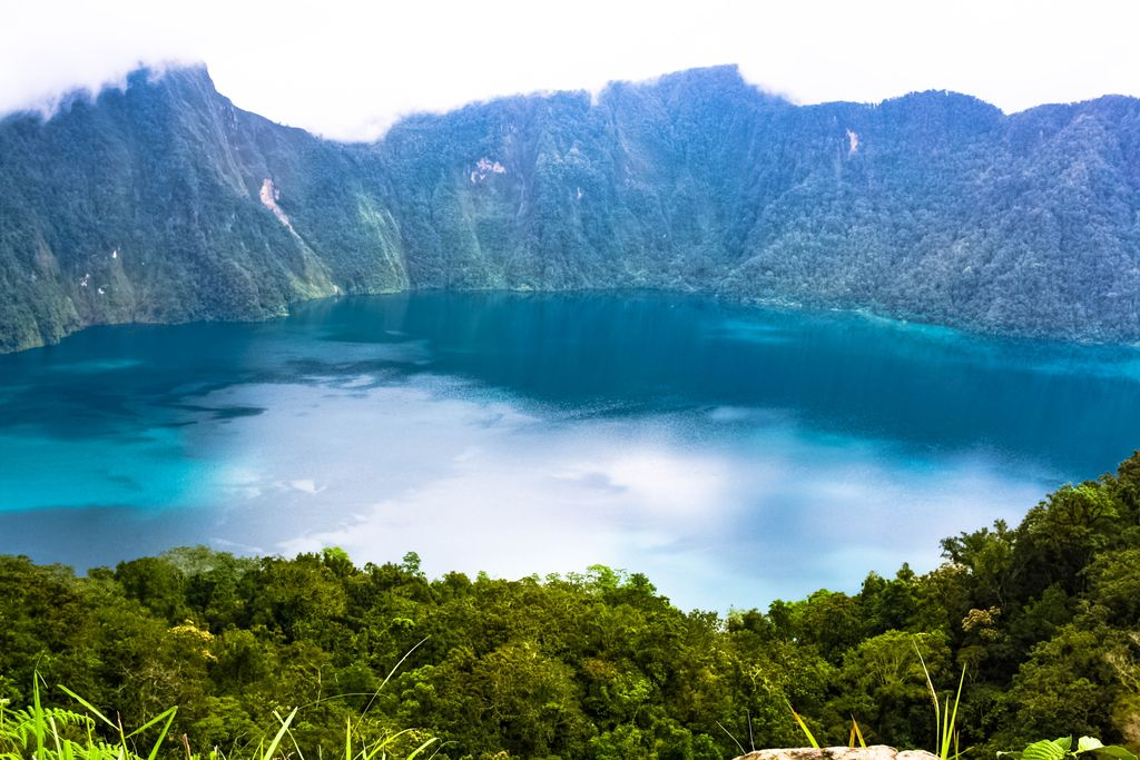 A lake with turquoise waters walled by green, vegetated cliffs