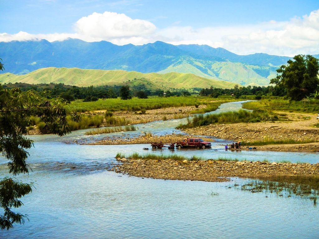 A river winds its way through vegetated fields and rocky shoals, backdropped by a dark and far-off mountain range, specifically the Caraballo Mountains, one of the mountain ranges of the Philippines