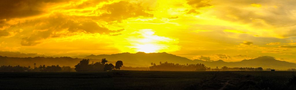 The sun sets behind a far-off mountain range, specifically the Daguma Mountain Range, one of the mountain ranges of the Philippines