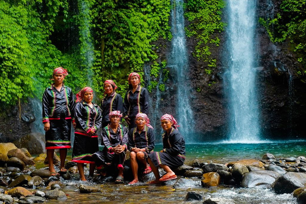Native folk in their indigenous attire pose before a waterfall cascading from a vegetated cliff