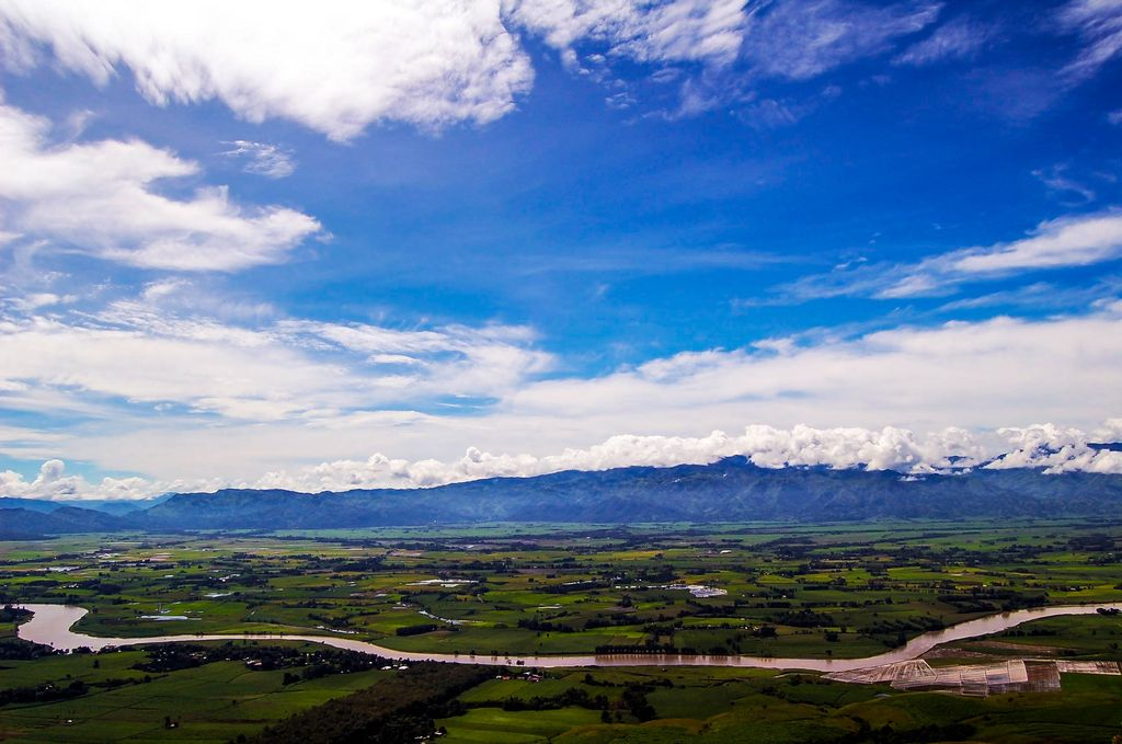 A winding river flows through a flat land with fields and farms, backdropped by a long and far-off mountain range, namely the Pantaron Mountain Range, one of the major mountain ranges of the Philippines