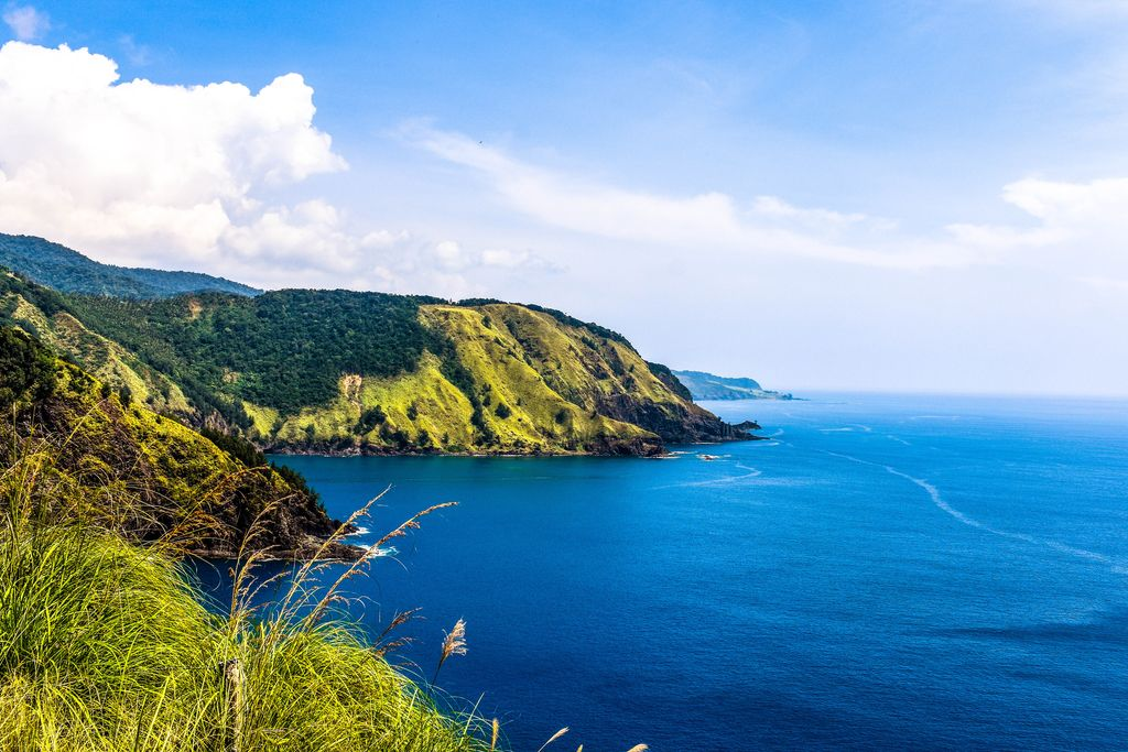 Green coastal cliffs fronting a vast body of blue water