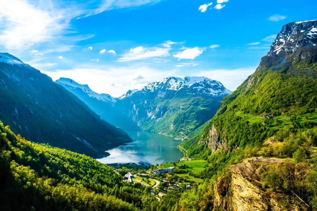 A view of a lake set in the midst of a a green forested valley and blue snow-capped mountains in Norway, home of friluftsliv