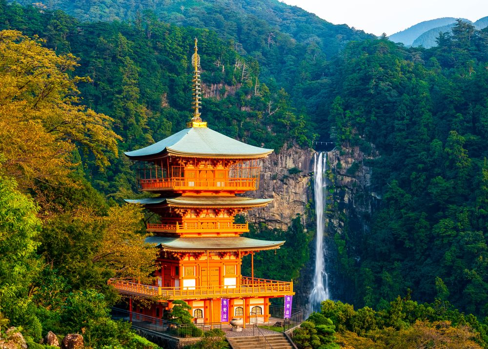 A Japanese pagoda stands surrounded by a trees and lush vegetation, and green mountains from which flow forth a waterfall