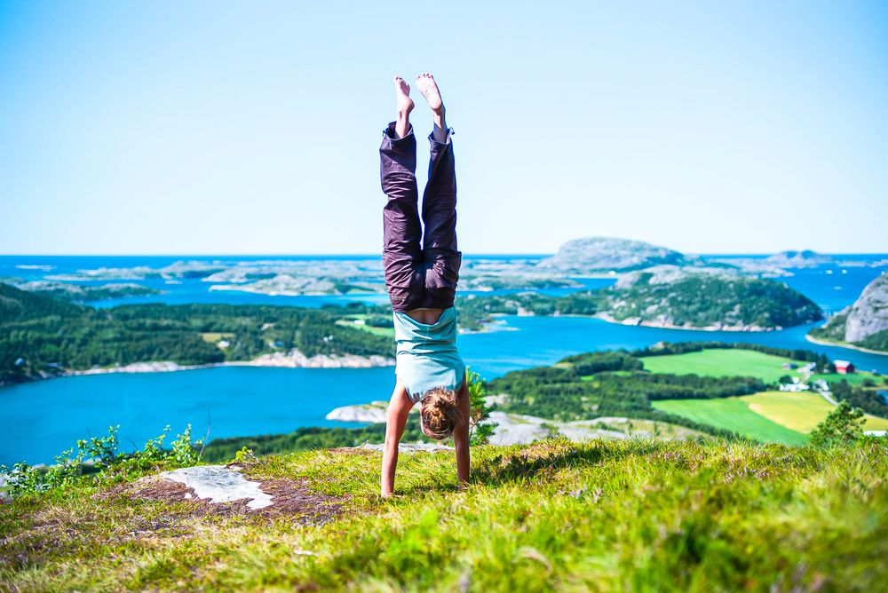 A woman does a handstand upon a grassy high ground overlooking a series of islands in a body of water
