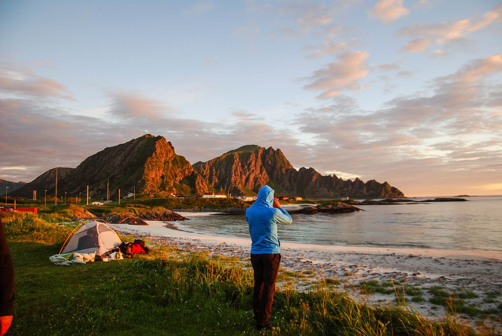 A man stands on a grassy shore, staring at the distant sea in Norway, home of friluftsliv