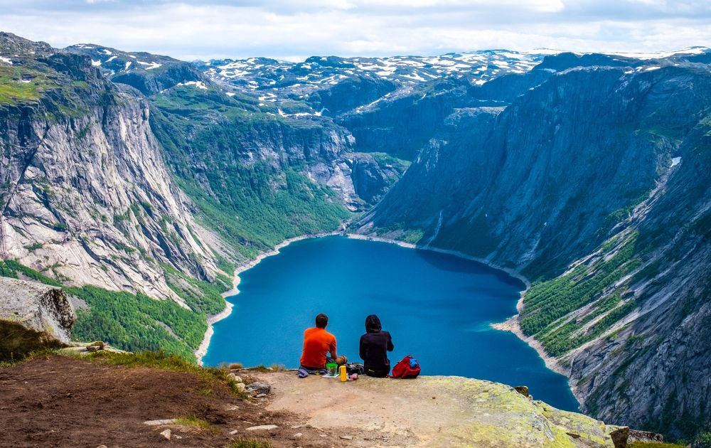 A couple sits on the edge of a cliff overlooking a blue lake set in the midst of a mountain crater in Norway, home of friluftsliv