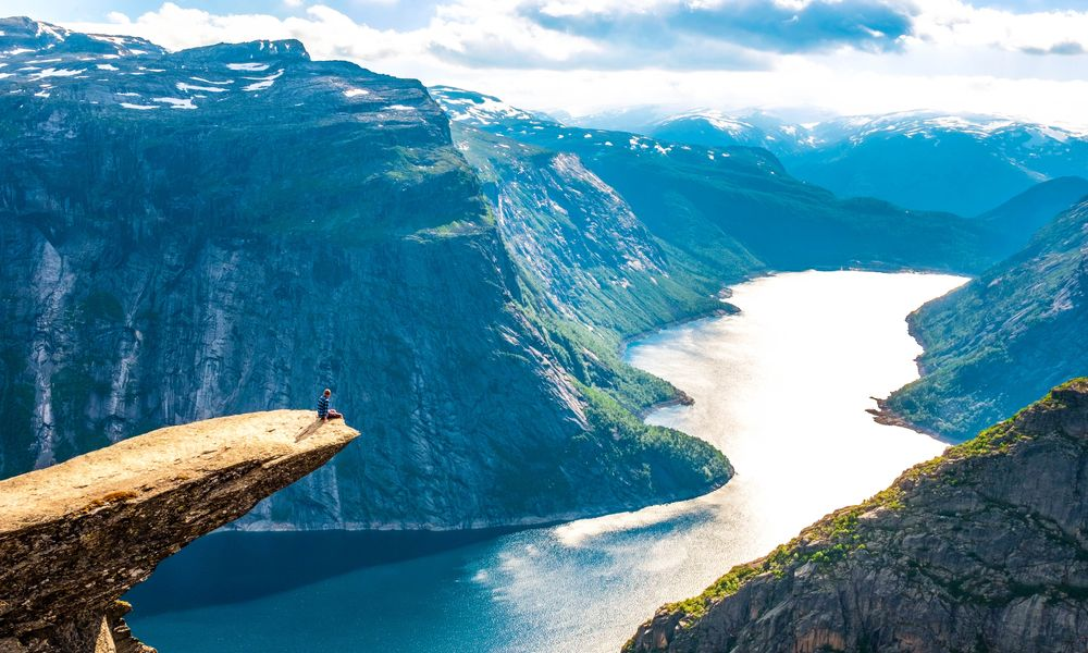 A man sits at the edge of a long, protruding rock overlooking a wide river walled by steep cliffs