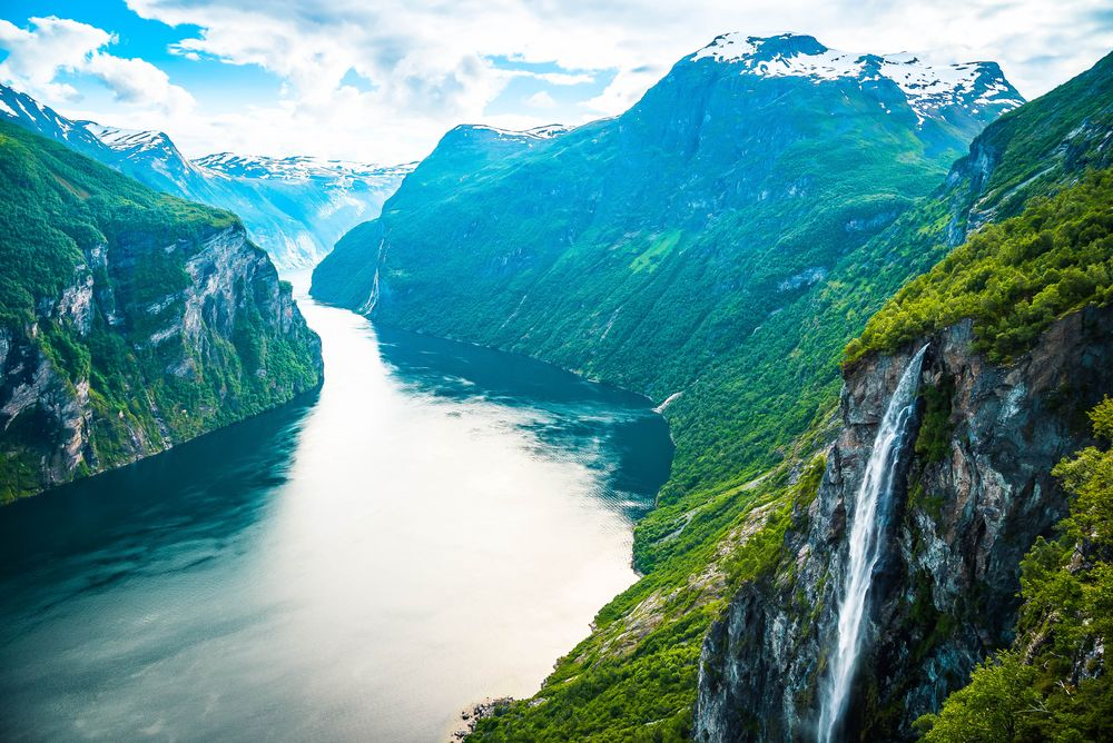 A view of a river running between steep mountain cliffs clad with vegetation in Norway, home of friluftsliv