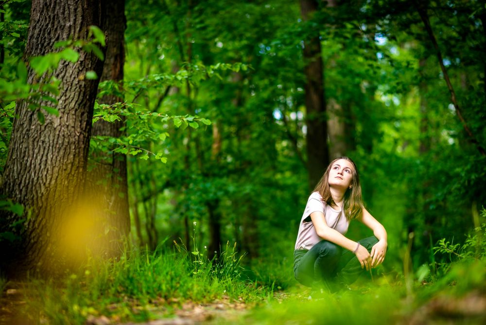 A woman sitting on the forest floor, surrounded by greener, gazes upwards; she is perhaps in the midst of shinrin-yoku, or forest bathing