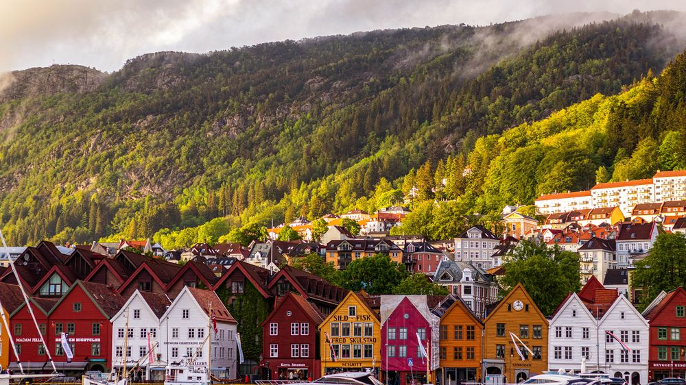 A view of rows upon rows of colorful buildings and houses, behind which rises a densely forested mountain slope in Norway, home of friluftsliv