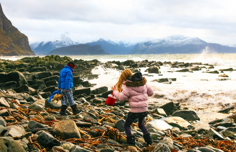 Two children walking among the rocks of a very stony beach that is buffeted by strong white waves; perhaps they are living out friluftsliv early on