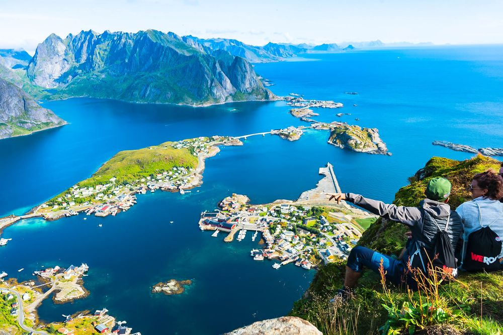 A couple sitting atop a grassy cliff, overlooking a series of developed islands in the middle of blue waters and distant mountains in Norway, home of friluftsliv