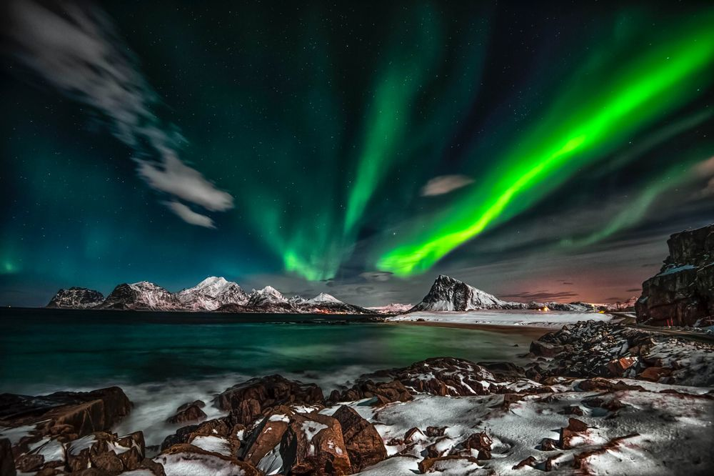 A rocky shore backdropped by snowy mountains beneath a night sky illuminated in the green hues of the Northern Lights