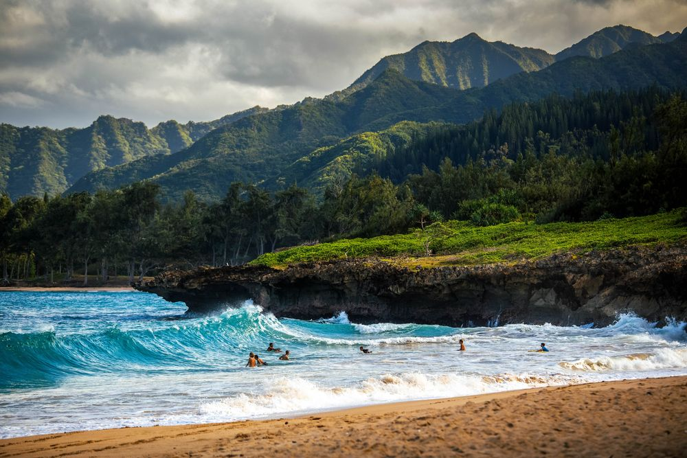 People frolic in white-capped turquoise waves washing along a sandy beach, while in the distance lofty, green hills and mountains stand beneath a lowering sky
