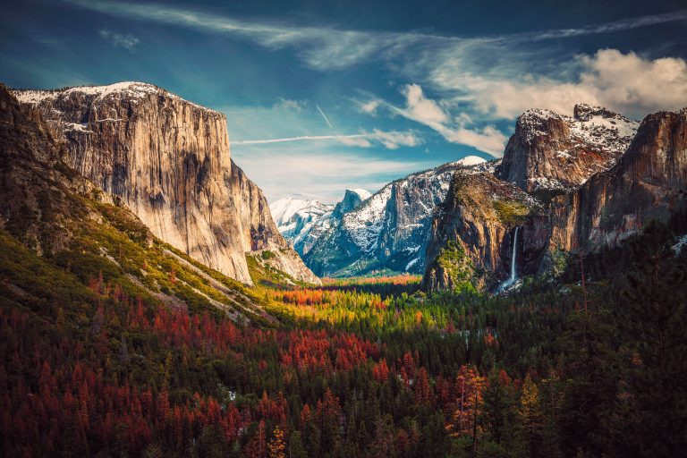 A forested valley of trees in autumn, walled on either side by lofty rock cliffs, beyond which rise the mountains of California