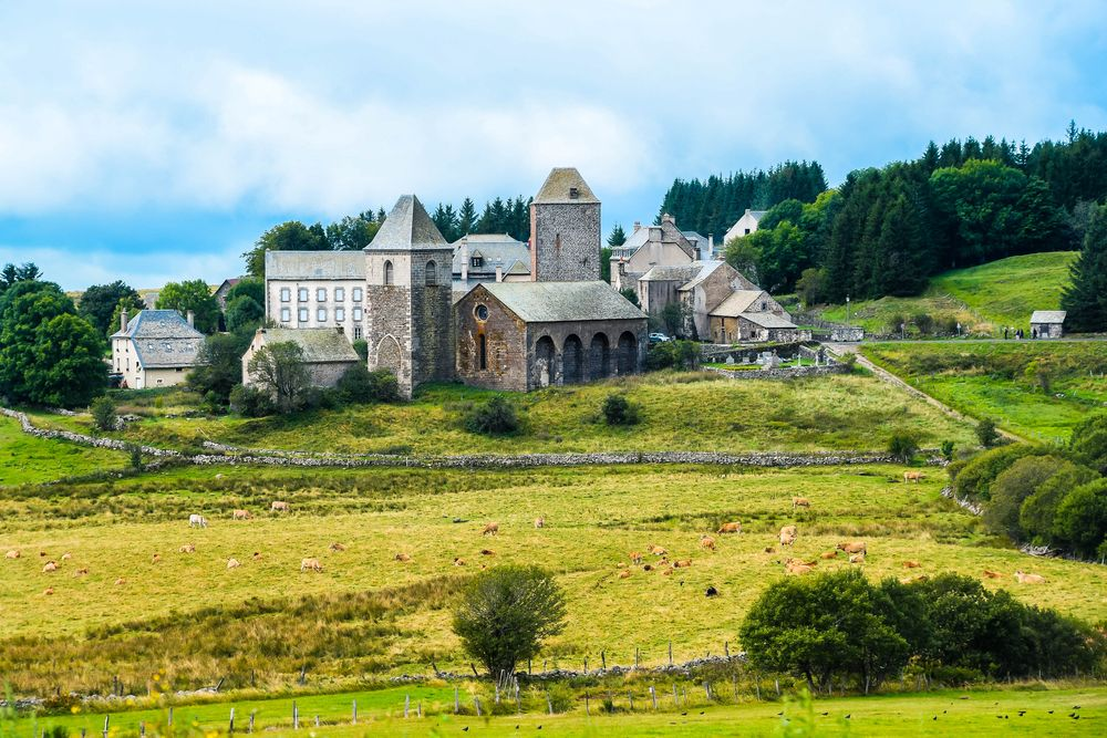 A little village with stone houses and stone churches in the middle of a grassy and wooded field, one of the settings described in Robert Louis Stevenson's Travels with a Donkey in the Cevennes