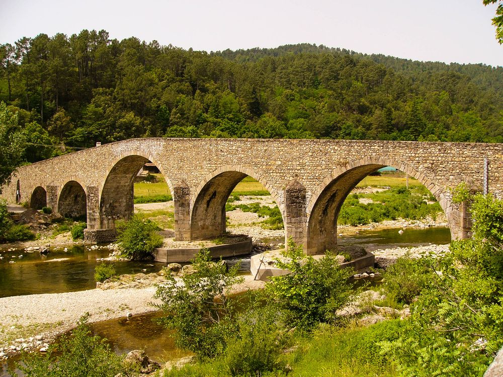 A long, humped stone bridge with multiple arches spanning a well-vegetated river, one of the settings described in Robert Louis Stevenson's Travels with a Donkey in the Cevennes