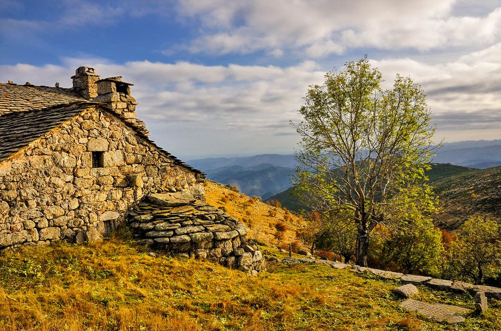A crude stone house built on a hillside overlooking a mountainous landscape, one of the settings described in Robert Louis Stevenson's Travels with a Donkey in the Cevennes