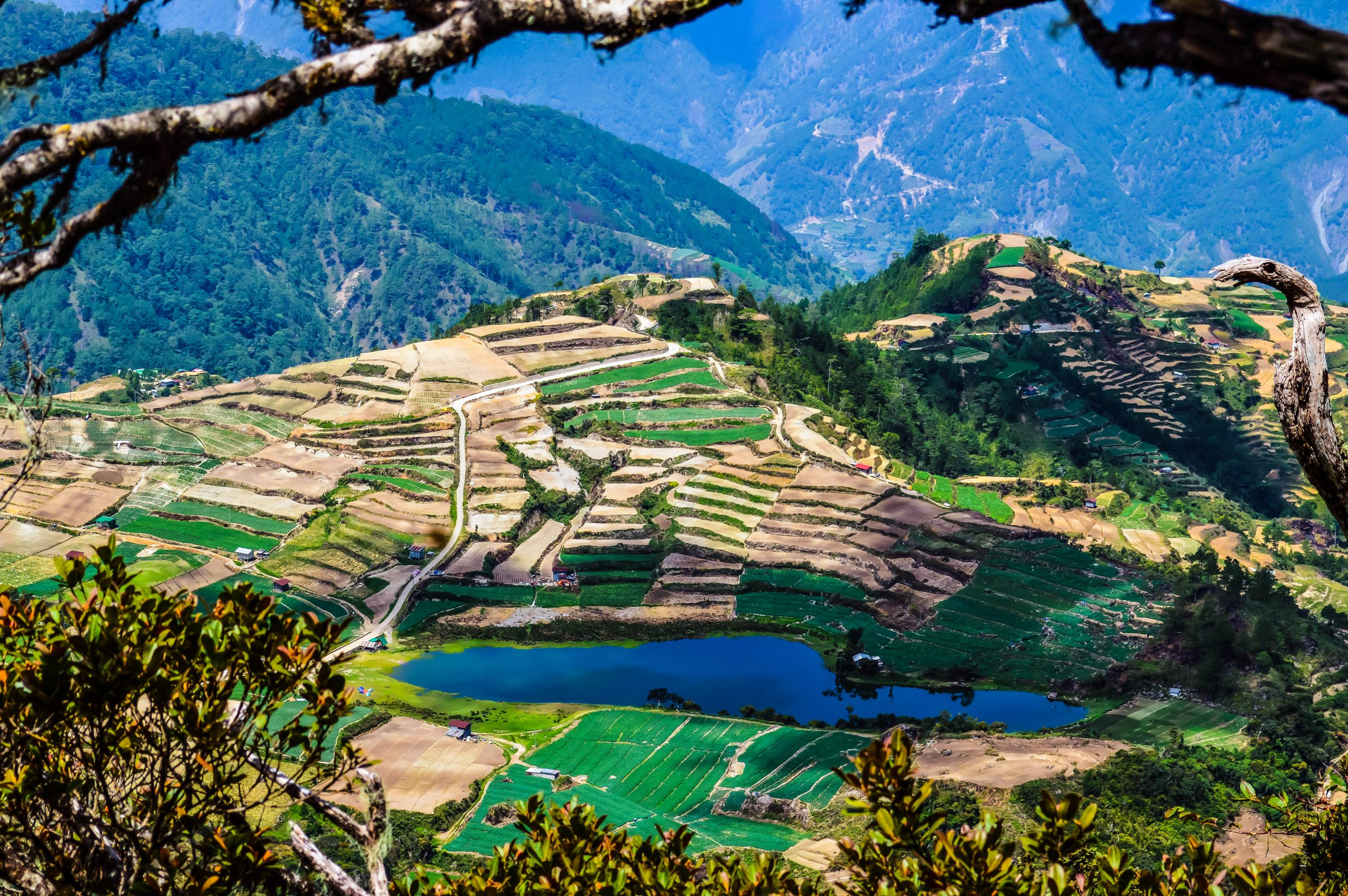A bird's eyeview of a lake on top of a high mountain, surrounded by farms, gardens, and terraces