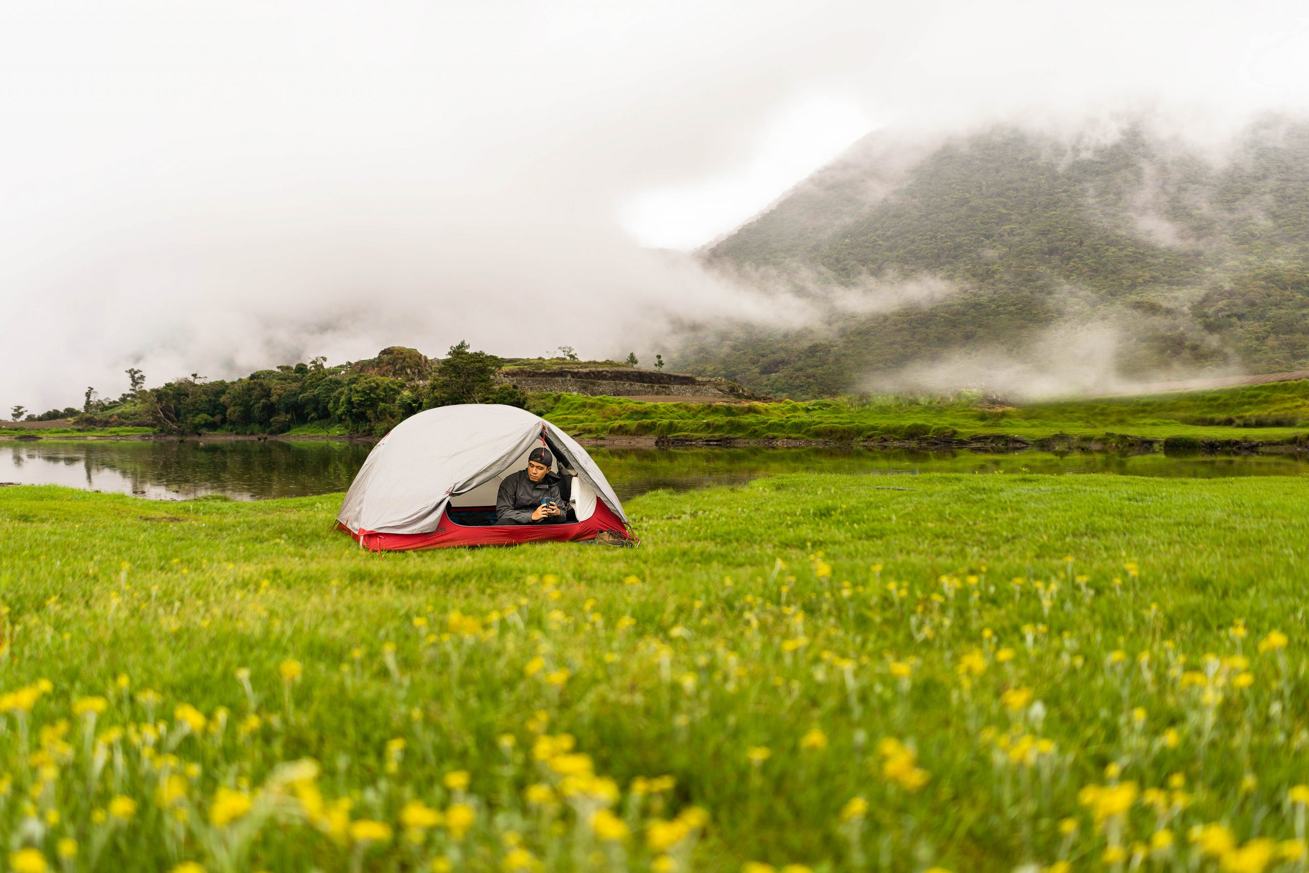 A camper's tent is pitched in the middle of a grassy field with yellow flowers, behind which rises a forested mountain (Mount Tabayoc, one of the highest mountains in the Philippines) covered in fog