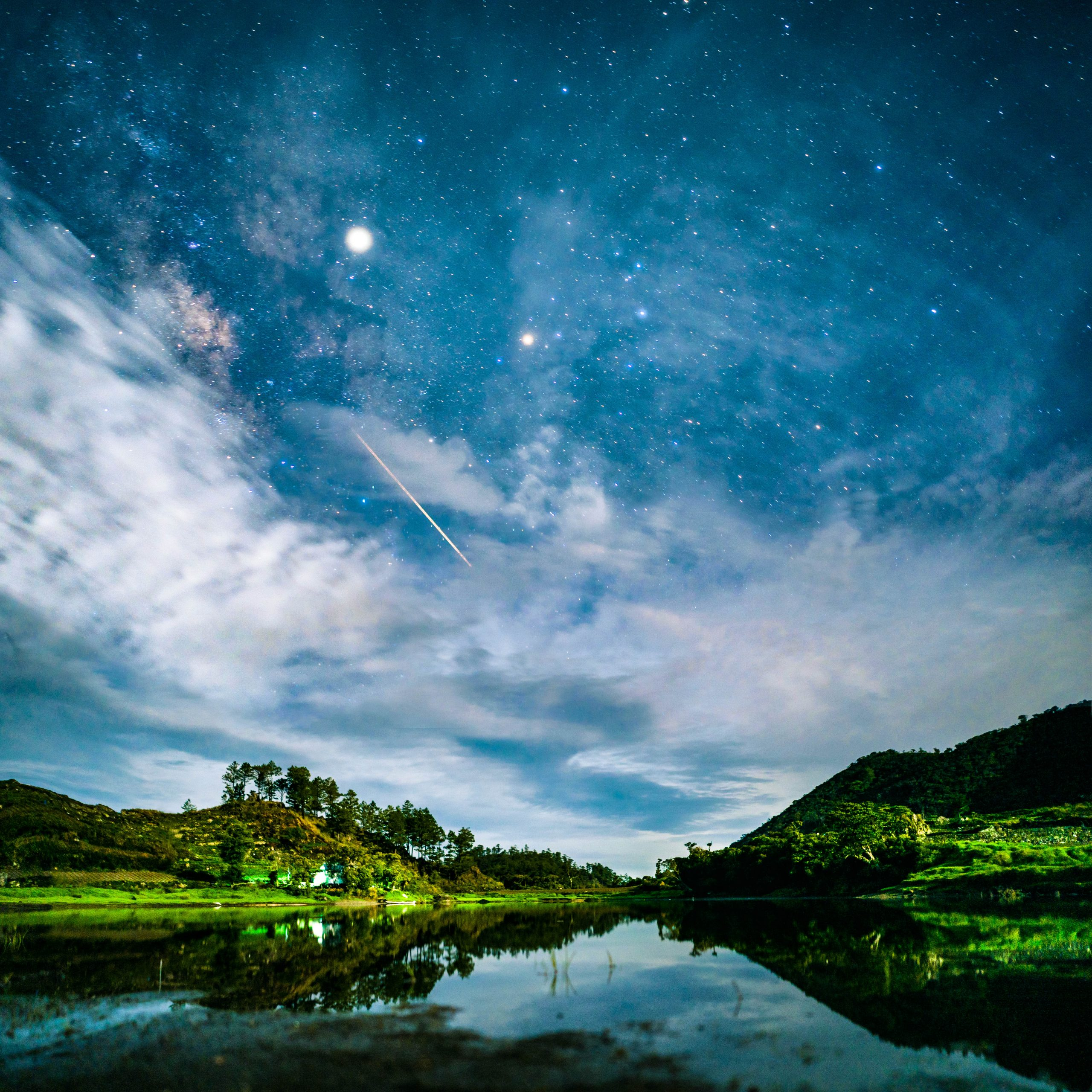 A view of a lake beneath a night sky full of stars