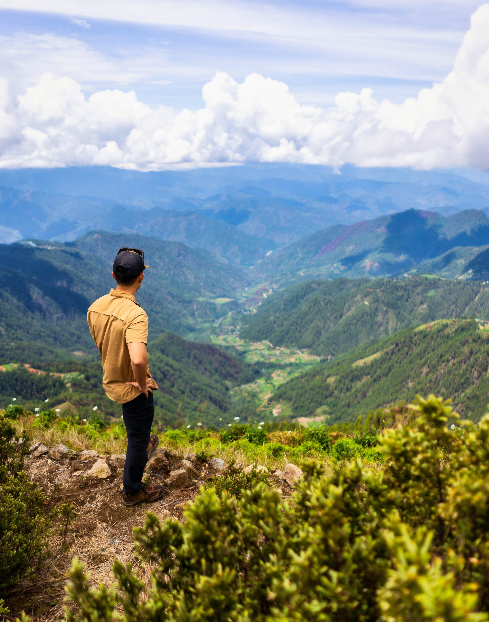 A man stands on high ground overlooking a green and mountainous landscape laid out beneath a cloudy sky
