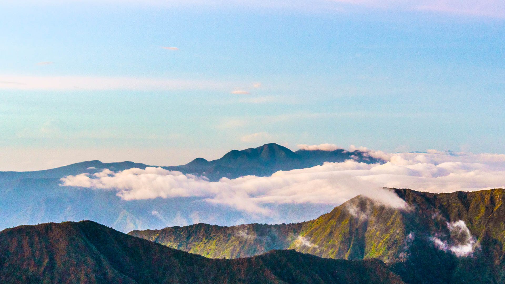 The jagged peaks of mountain (Mount Kalatungan, one of the highest mountains in the Philippines) rises high above a layer of white clouds