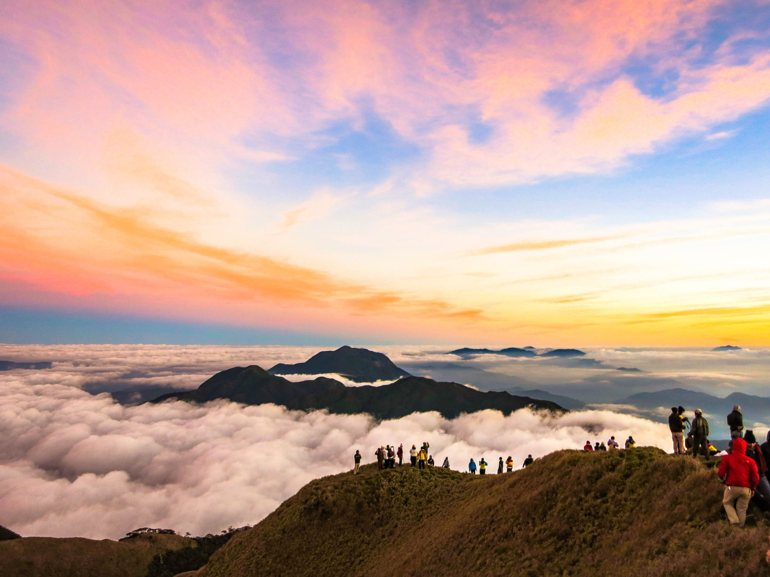 Groups of people stand upon a lofty ridge overlooking a mountainous landscpe covered in clouds