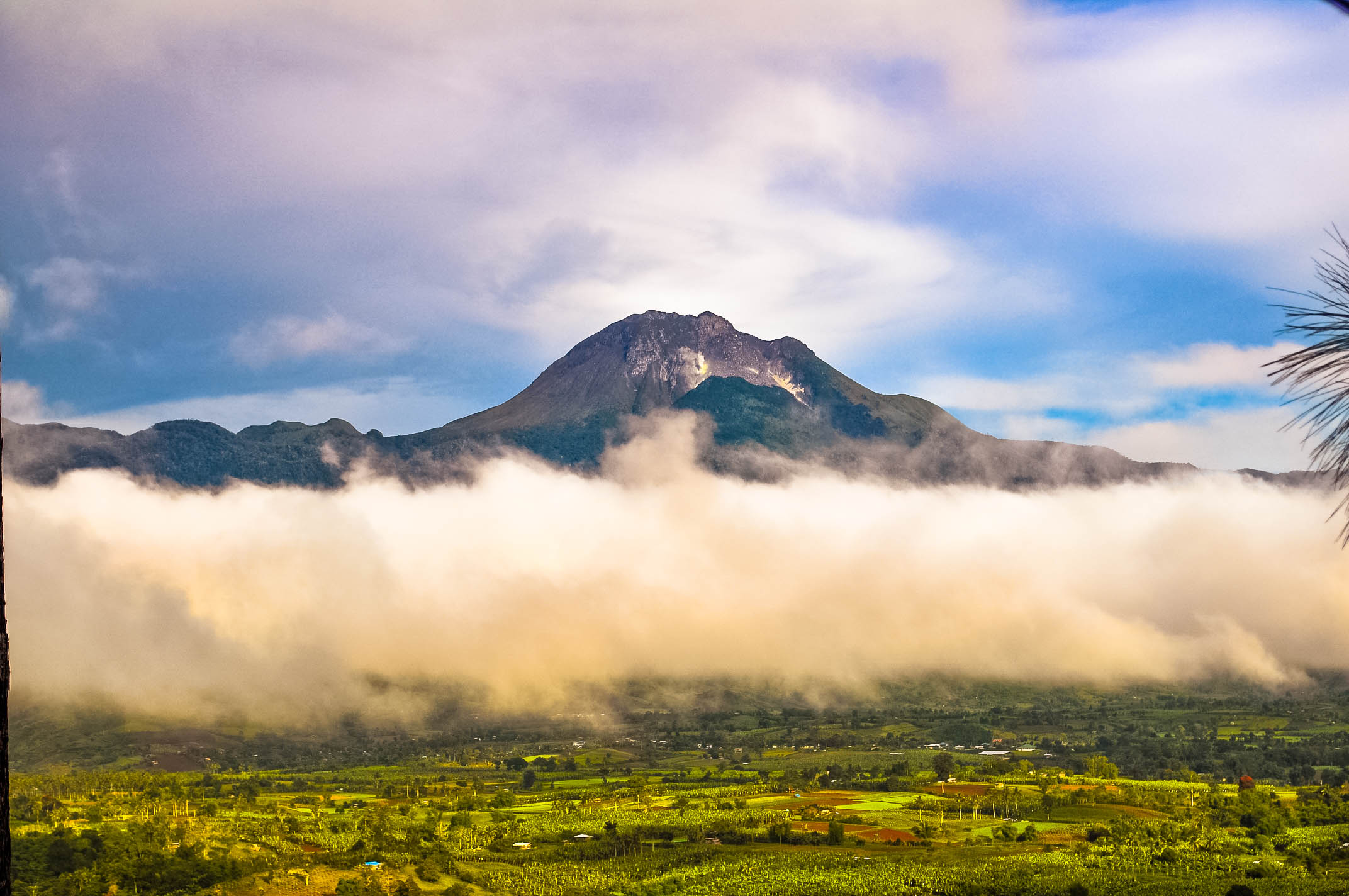 The peak of a lofty mountain (that of Mount Apo, the highest mountain in the Philippines), rises above the green plain and above a swath of white cloud